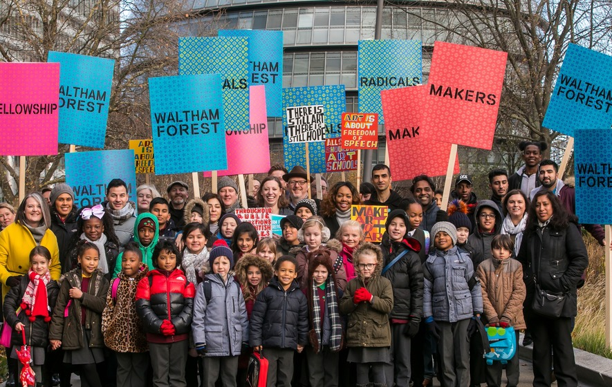 Waltham Forest's history and heritage of radicals and creators like William Morris. Councillor Clare Coghill, Leader of Waltham Forest Council, with local residents including artist Bob and Roberta Smith and school children, holding placards: Fellowship, Makers, Radicals, Waltham Forest.